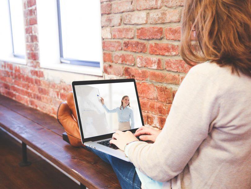 Nainen istuu työpöydän äärellä sylissään tietokone, josta hän seuraa opetusta.