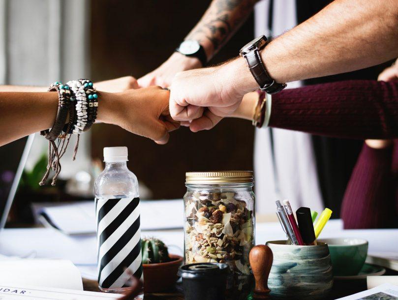 viisi kättä, jotka tekevät nyrkkitervehdyksen yhteistyön merkiksi