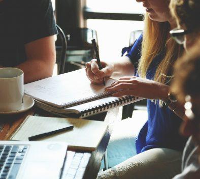 ihmiset istuvat pöydän ääressä yhdessä, pohtivat asioita ja tekevät muistiinpanoja